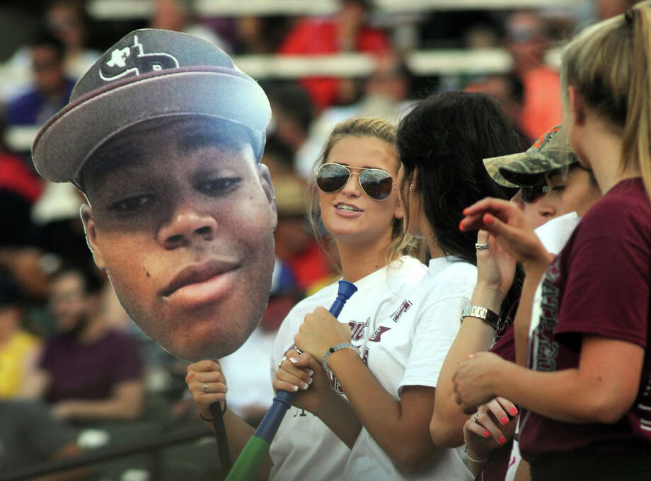 George Ranch High School senior Mackenzie Kearns, from left, holds a fathead of Longhorn senior rightfielder Stone Garrett for Garrett's girlfriend, Sutton Holstein, also a GRHS senior during GRHS's Class 4A 2014 UIL Baseball State Championships matchup versus Victoria East at Dell Diamond in Round Rock on Thursday. Photo: Jerry Baker, For The Chronicle