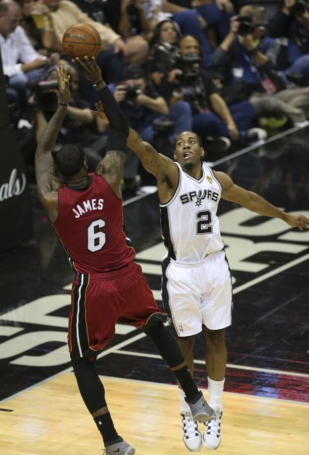 San Antonio Spurs' Kawhi Leonard extends to defends a shot by Miami Heat's LeBron James during the first half at the AT&T Center, Thursday, June 5, 2014. T Photo: Jerry Lara, San Antonio Express-News