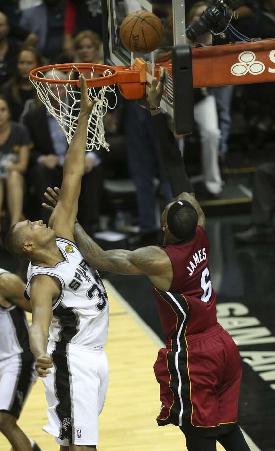 Miami Heat's LeBron James tries to score as San Antonio Spurs' Boris Diaw defends during the second half at the AT&T Center, Thursday, June 5, 2014. The Spurs won 110-95 to lead the series 1-0. After the shot, Lebron left the game with leg cramps. Photo: Jerry Lara, San Antonio Express-News