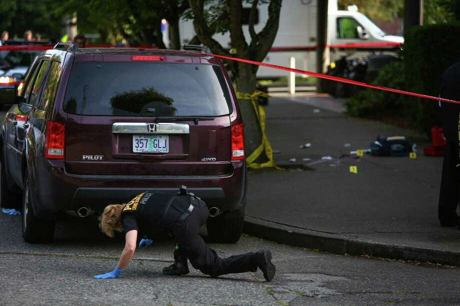 An investigator looks under a car after a shooting at Seattle Pacific University on Thursday, June 5, 2014. Photo: JOSHUA TRUJILLO, SEATTLEPI.COM / SEATTLEPI.COM