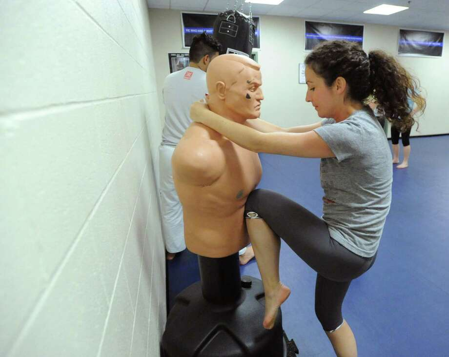 Greenwich Time reporter Brittany Lyte knees a self-defense dummy during a Women's Self-Defense class at the Greenwich Police Department, Thursday night, June 5, 2014. Photo: Bob Luckey / Greenwich Time