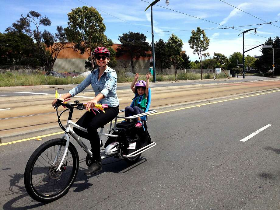 Kristin Smith, communications director for the San Francisco Bicycle Coalition, takes Olina, 5, for a ride on an electric-assist bike during Sunday Streets in the Bayview. Photo: Rebeka Rodriguez