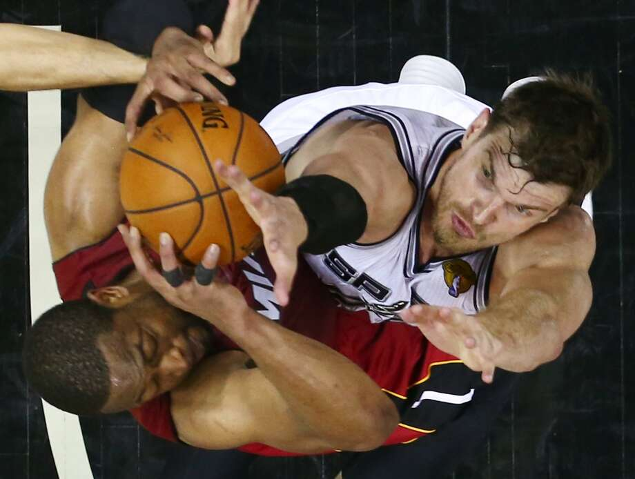 Heat guard Dwyane Wade, left, and Spurs center Tiago Splitter go after the rebound. Photo: Andy Lyons, Associated Press