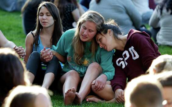 Students from Seattle Pacific University gather outside in a spontaneous prayer circle after a church service was full, following a shooting on the campus of the university Thursday, June 5, 2014, in Seattle. A lone gunman armed with a shotgun opened fire in a building on the campus, killing one person before he was subdued by a student as he tried to reload, police said. Police say the student building monitor at the university disarmed the gunman and several other students held him until police arrived at the Otto Miller building. Photo: Elaine Thompson, AP / AP
