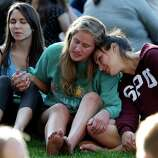 Students from Seattle Pacific University gather outside in a spontaneous prayer circle after a church service was full, following a shooting on the campus of the university Thursday, June 5, 2014, in Seattle. A lone gunman armed with a shotgun opened fire in a building on the campus, killing one person before he was subdued by a student as he tried to reload, police said. Police say the student building monitor at the university disarmed the gunman and several other students held him until police arrived at the Otto Miller building.