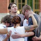 Students and faculty pray together following a shooting on the campus of Seattle Pacific University Thursday, June 5, 2014, in Seattle. Seattle police now say there are four victims in a shooting and say one suspect is in custody. Police say one man and one woman have life-threatening injuries while another man and another woman are reported in stable condition.
