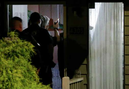 With guns drawn, police officers enter a home believed to be tied to Aaron R. Ybarra, who was arrested Thursday, June 5, 2014 following a shooting at Seattle Pacific University in Seattle. Photo: Ted S. Warren, AP / AP