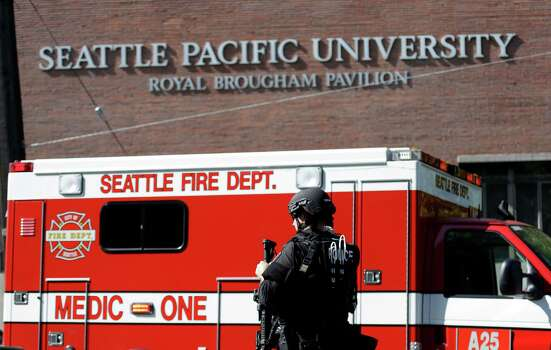 A Seattle police SWAT team member walks toward a campus building following a shooting at Seattle Pacific University on Thursday, June 5, 2014, in Seattle. A lone gunman armed with a shotgun opened fire in a building on the campus, killing one person before he was subdued by a student as he tried to reload, police said. Police say the student building monitor at the university disarmed the gunman and several other students held him until police arrived at the Otto Miller building. Photo: Elaine Thompson, AP / AP2014