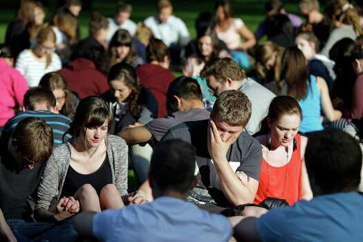 Students from Seattle Pacific University gather outside in a prayer circle after a church service was full following a shooting on the university campus Thursday, June 5, 2014, in Seattle. A lone gunman armed with a shotgun and a knife opened fire in a building on the campus, killing one person before he was subdued with pepper spray by a student as he tried to reload, police said. Photo: Elaine Thompson, AP / AP2014