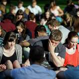 Students from Seattle Pacific University gather outside in a prayer circle after a church service was full following a shooting on the university campus Thursday, June 5, 2014, in Seattle. A lone gunman armed with a shotgun and a knife opened fire in a building on the campus, killing one person before he was subdued with pepper spray by a student as he tried to reload, police said.