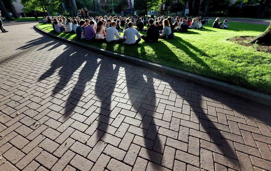 Students from Seattle Pacific University gather outside in a prayer circle after a nearby church service was full following a shooting on the campus of the university Thursday, June 5, 2014, in Seattle. A lone gunman armed with a shotgun and a knife opened fire in a building on the campus, killing one person before he was subdued with pepper spray by a student as he tried to reload, police said. Photo: Elaine Thompson, AP / AP2014