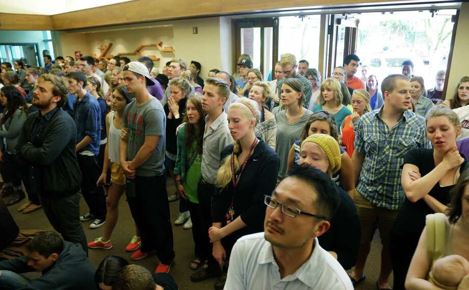 People stand in the foyer during a prayer service at the First Free Methodist Church Thursday, June 5, 2014 at Seattle Pacific University in Seattle, where a shooting took place Thursday afternoon. Photo: Ted S. Warren, AP / AP