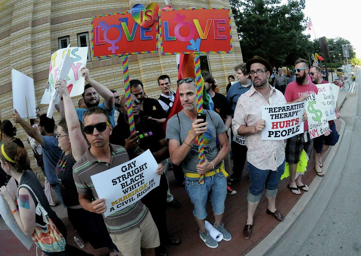 """People hold signs during a same sex marriage rally outside the Texas GOP convention in Fort Worth in 2014.Texas Republican Party principles include a defense of traditional marriage """"of a natural man and a natural woman.""""(AP Photo/The Fort Worth Star-Telegram, Max Faulkner)"""