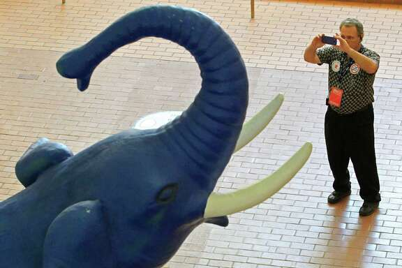 Delegate and registration volunteer Mark Liberto, from Arlington, Texas, pauses to make a photo of the large GOP elephant at the convention center west entrance as people arrive, Wednesday, June 4, 2014, for the Republican Party of Texas state convention (starting Thursday, June 5) at the Fort Worth Convention Center in Fort Worth, Texas. (AP Photo/Star-Telegram, Paul Moseley) MAGAZINES OUT; (FORT WORTH WEEKLY, 360 WEST); INTERNET OUT.