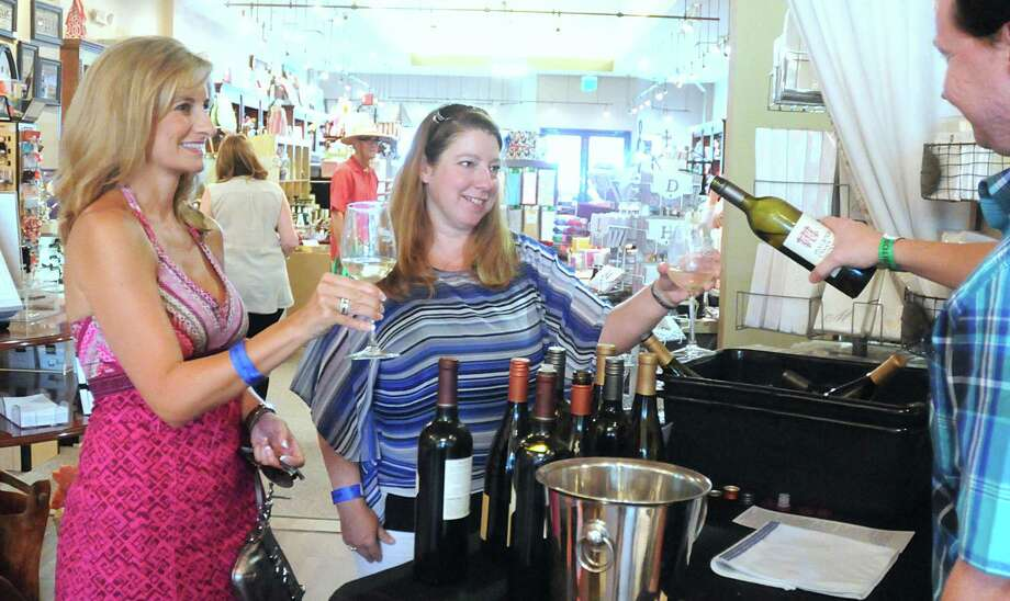 Shanna Davis and Chantele Sinnett, both of The Woodlands try a sample of wine from Addison Martin inside of Zulees store during the H-E-B Wine Walk, at Market Street in The Woodlands. The Wine Walk is part of the Wine & Food Week events in The Woodlands.  Over 40 wine tasting stations, with more than 150 wines and craft beers were featured during the event. Photo: David Hopper, For The Chronicle / freelance