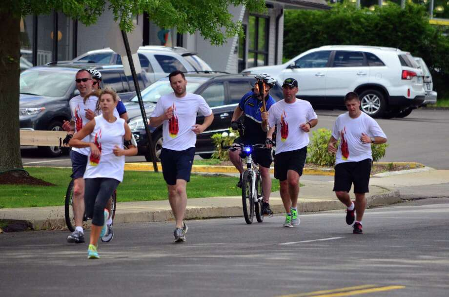 Darien and New Canaan police officers carried the torch along the Post Road for the start of the Special Olympics which start  on Friday, June 6 at Southern Connecticut State University. Photo: Megan Spicer / Darien News