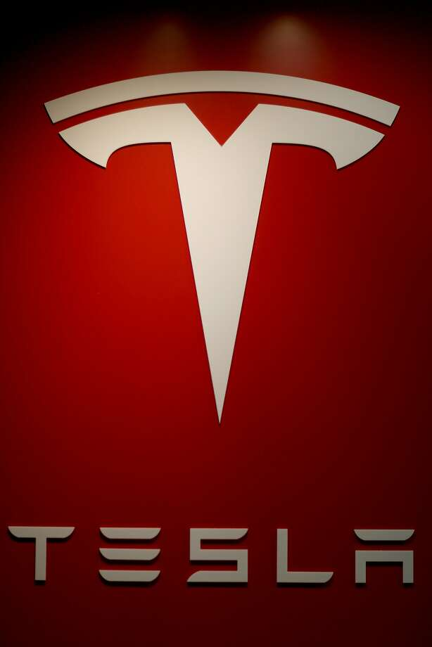 A sign is seen in theTesla Motors vehicle showroom at the Dadeland Mall on February 19, 2014 in Miami, Florida.  Tesla said today it earned $46 million in the fourth quarter on a non-adjusted basis, or 33 cents a share, causing shares in the company to jump 12 percent.  (Photo by Joe Raedle/Getty Images) Photo: Joe Raedle, Getty Images