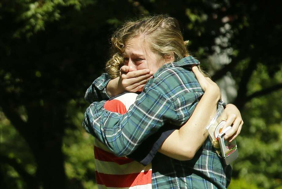 Two women embrace near a prayer circle on the campus of Seattle Pacific University. Classes were canceled Friday, a day after a gunman killed one person and injured two others. Photo: Ted S. Warren, Associated Press