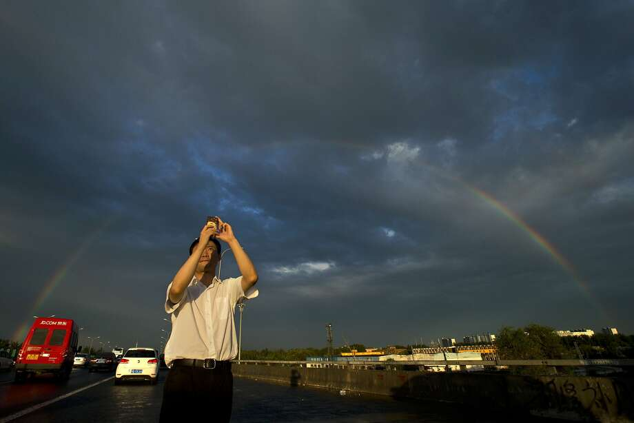 In Beijing, just seeing blue sky through the smog is a thrill:A man stops on a Beijing 
