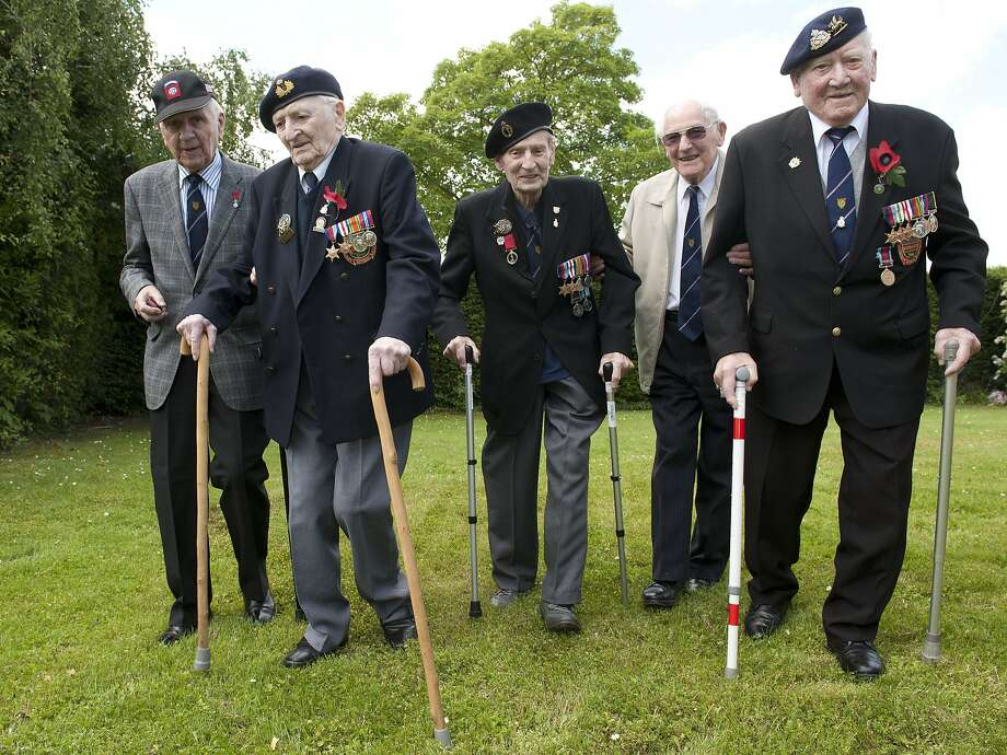 Back to Normandy: Most walking with two canes, British veterans of the D-Day invasion (from left) Sgt. Ken Reynolds, 90; Able 