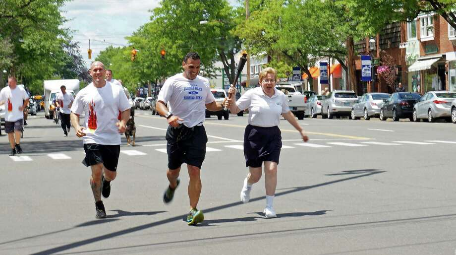 "Police officers and Special Olympics athletes carry the ""Flame of Hope"" torch during the Law Enforcement Torch Run Friday. The run started in Greenwich and ended in New Haven. Photo: Genevieve Reilly / Fairfield Citizen"
