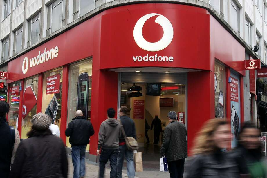 Pedestrians in London walk by a branch of Vodafone, a large telecommunications company. Photo: Sang Tan, Associated Press