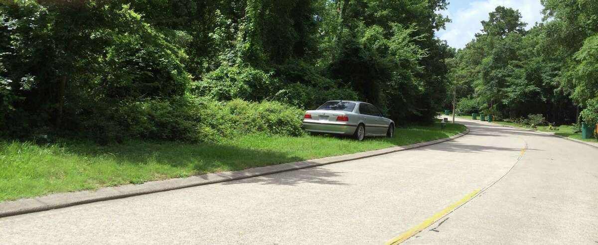 A vehicle is parked on the grassy strip of land that runs along Rush Haven Drive in the Indian Springs neighborhood of The Woodlands. Vehicle owners now face a fine of up to $500 or a towed vehicle for leaving cars parked in open space reserves or on other Township property.