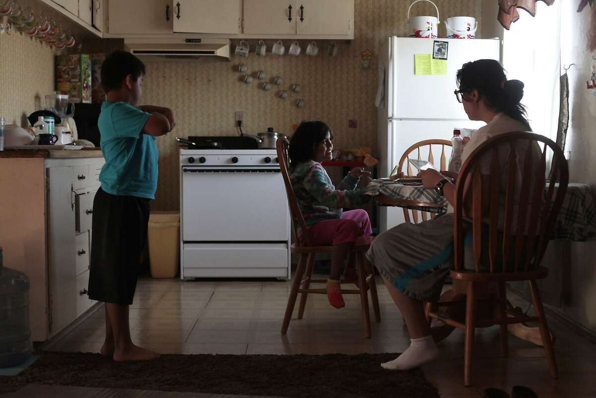 Left to right, Isaac, Natalia and Joanna Lopez chat over breakfast at their home in Hayward, Calif. on Thursday, June 5, 2014. Lopez has difficulty making ends meet while only making $9.20 an hour at Wal-Mart.