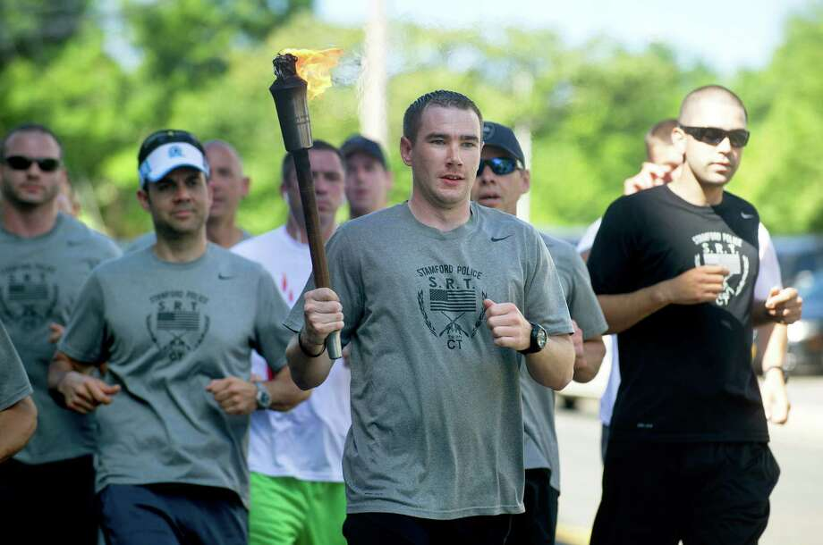"Stamford police officer Brendan Phillips runs with the Special Olympics ""flame of hope"" and other officers through the city to the WWE where they briefly stopped for a rally and passed the torch to Darien officers on Friday, June 6, 2014. Photo: Lindsay Perry / Stamford Advocate"