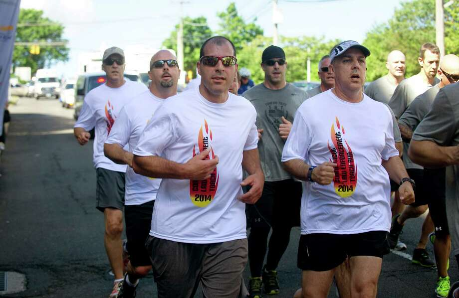 "Stamford police officers run with the Special Olympics ""flame of hope"" through the city to the WWE where they briefly stopped for a rally and passed the torch to Darien officers on Friday, June 6, 2014. Photo: Lindsay Perry / Stamford Advocate"