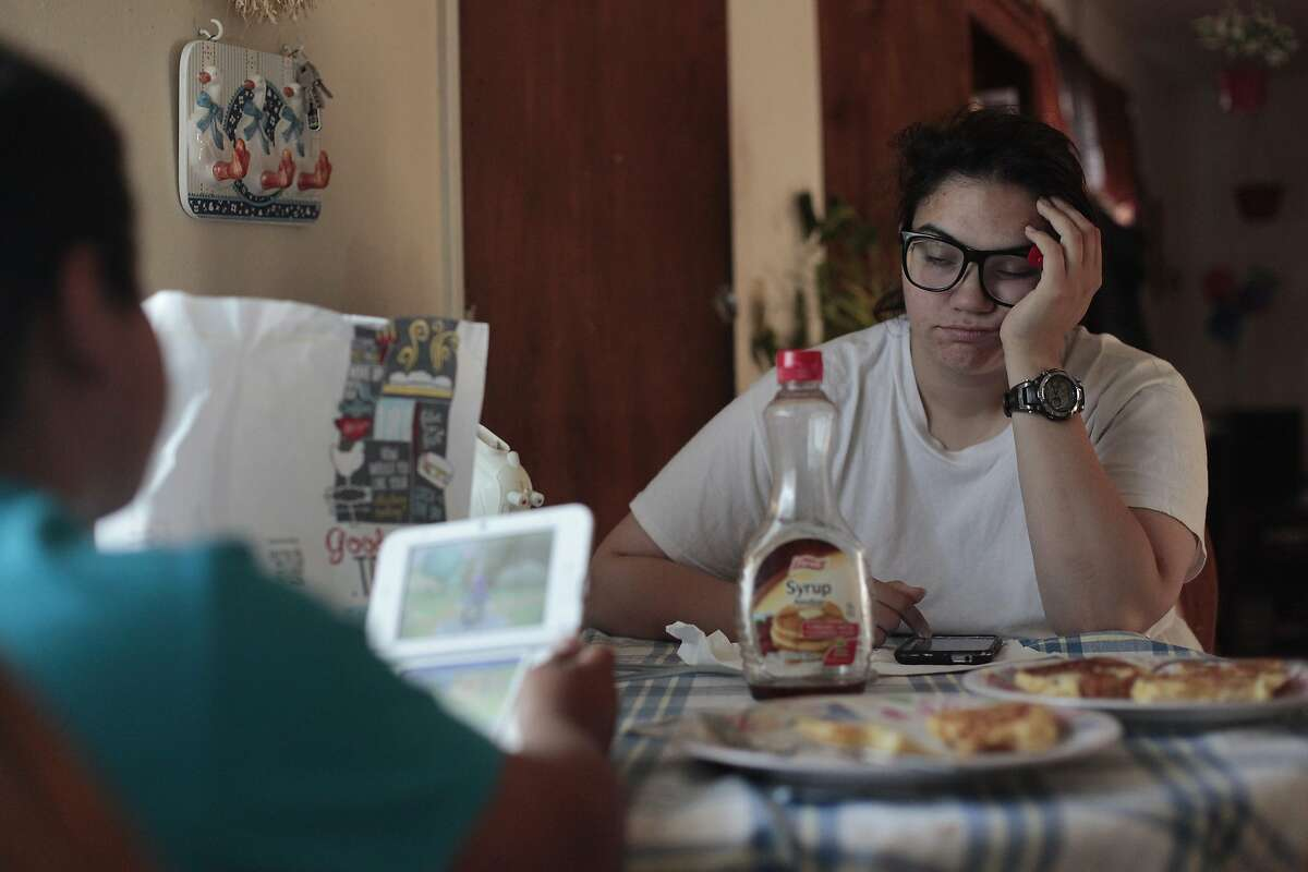 Joanna Lopez rests her eyes as her son Isaac eats his breakfast in Hayward, Calif. on Thursday, June 5, 2014. Lopez has difficulty making ends meet while only making $9.20 an hour at Wal-Mart.