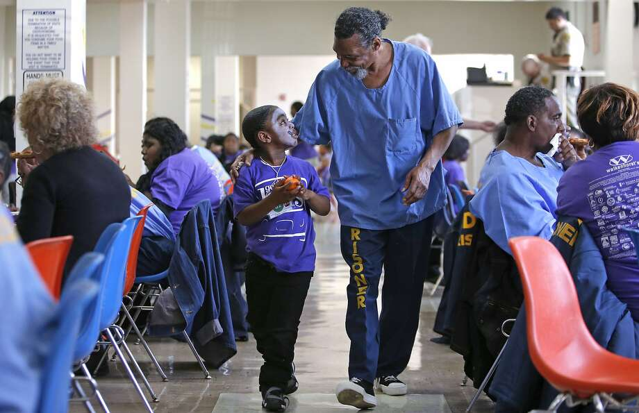 "Inmate Steve Sutton walks with his grandson Kelion Sutton, 5 during the visit inside San Quentin State Prison, on Friday June 6, 2014, in San Rafael, Ca. The 15th annual ""Get on the Bus"" program put on by the California Department of Corrections and the Center for Restorative Justice, that buses families from throughout California to San Quentin Prison to visit their fathers and husbands who are incarcerated there. Photo: Michael Macor, The Chronicle"
