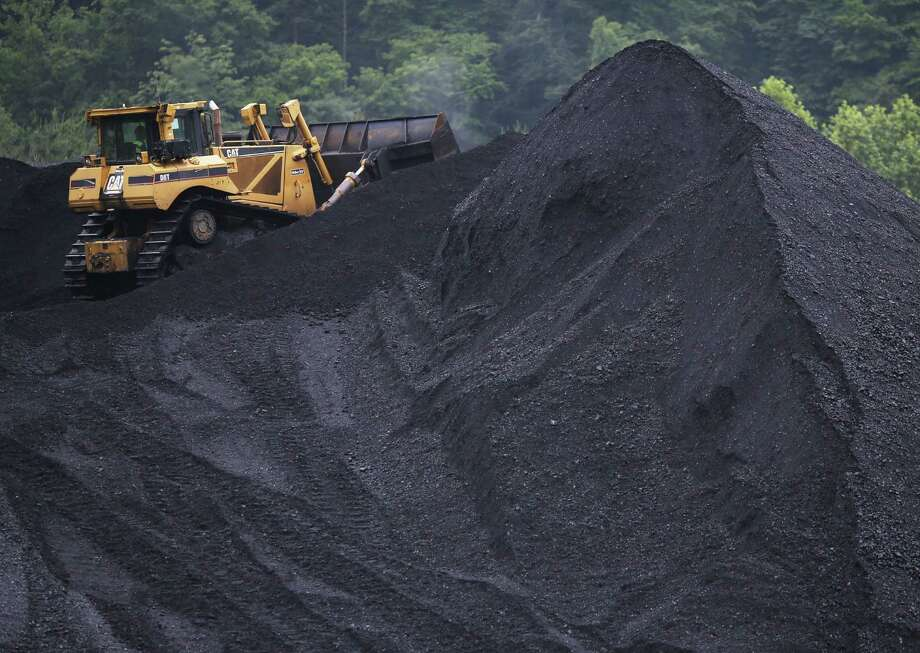 A bulldozer operates atop a coal mound in Shelbiana, Kentucky. New regulations on carbon emissions have reportedly angered politicians on both sides of the aisle in energy-producing states such as Kentucky and West Virginia. The region's economy has taken a big hit. Photo: Luke Sharrett / Getty Images / 2014 Getty Images
