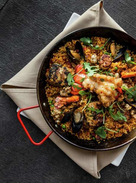 Arroz Mariscado is a new paella dish at Américas River Oaks that features grilled market fish, tempura lobster tail, scallop, shrimp and calamari over saffron and Spanish chorizo rice. Photo: Julie Soefer / Julie Soefer