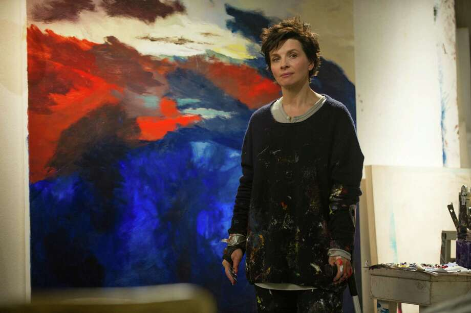 """Juliette Binoche stands before one of the canvases she painted in the new movie """"Words and Pictures."""" In the film, Binoche plays an art teacher whose rheumatoid arthritis forces her to find unorthodox measures to paint. Photo: DOANE GREGORY, HO / DOANE GREGORY"""