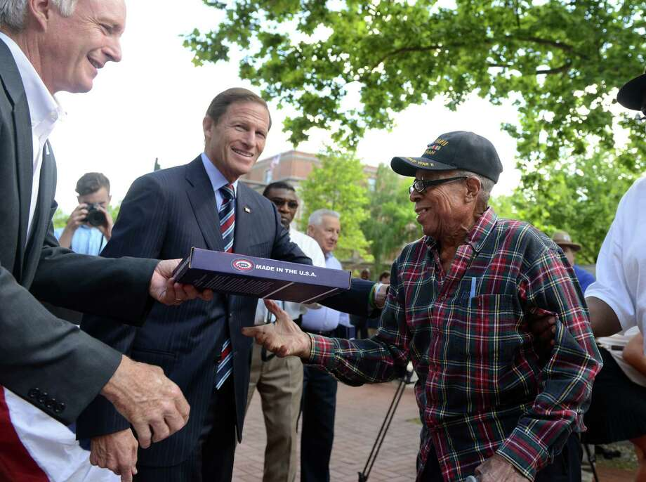 World War II veteran Frank Vallerini, of Bridgeport, born July 4, 1924, is presented with a flag from Mayor Bill Finch and Sen. Richard Blumenthal during a ceremony to mark the 70th anniversary of D-Day Friday, June 6, 2014, at the WWII Memorial in Col. Mucci Plaza in Bridgeport, Conn. Photo: Autumn Driscoll / Connecticut Post