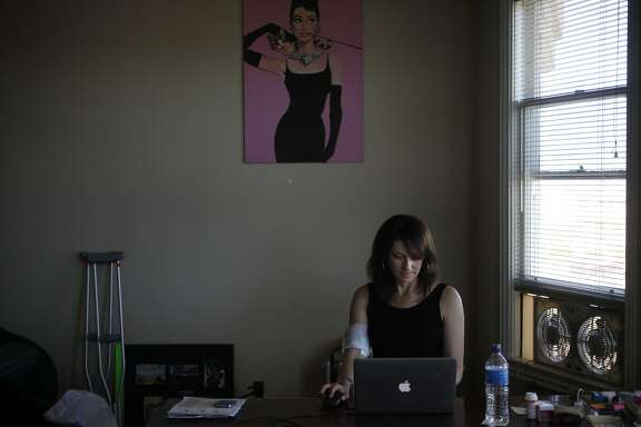 Beth Rifkin, 46, does work on her computer May 26, 2014 in her friend's apartment in San Francisco, Calif. Rifkin, who is a freelance writer, has been staying with a friend of hers since early May. She was given less than 24 hours to move out of a room she was living in through Airbnb in March after two months of living there with an established contract, according to Rifkin. Soon after moving into her friend's place temporarily, she had to be hospitalized due to an infection in her bone that had been festering from earlier infection she had in her foot in the fall, unbeknownst to Rifkin. Two and a half weeks and one surgery later, Rifkin was released from the hospital May 22 for a week. She will be re-admitted for a second surgery on May 29. Rifkin believes that part of the reason her infection came back in full force was due to the stress of not knowing her housing situation, causing pressure on her immune system.