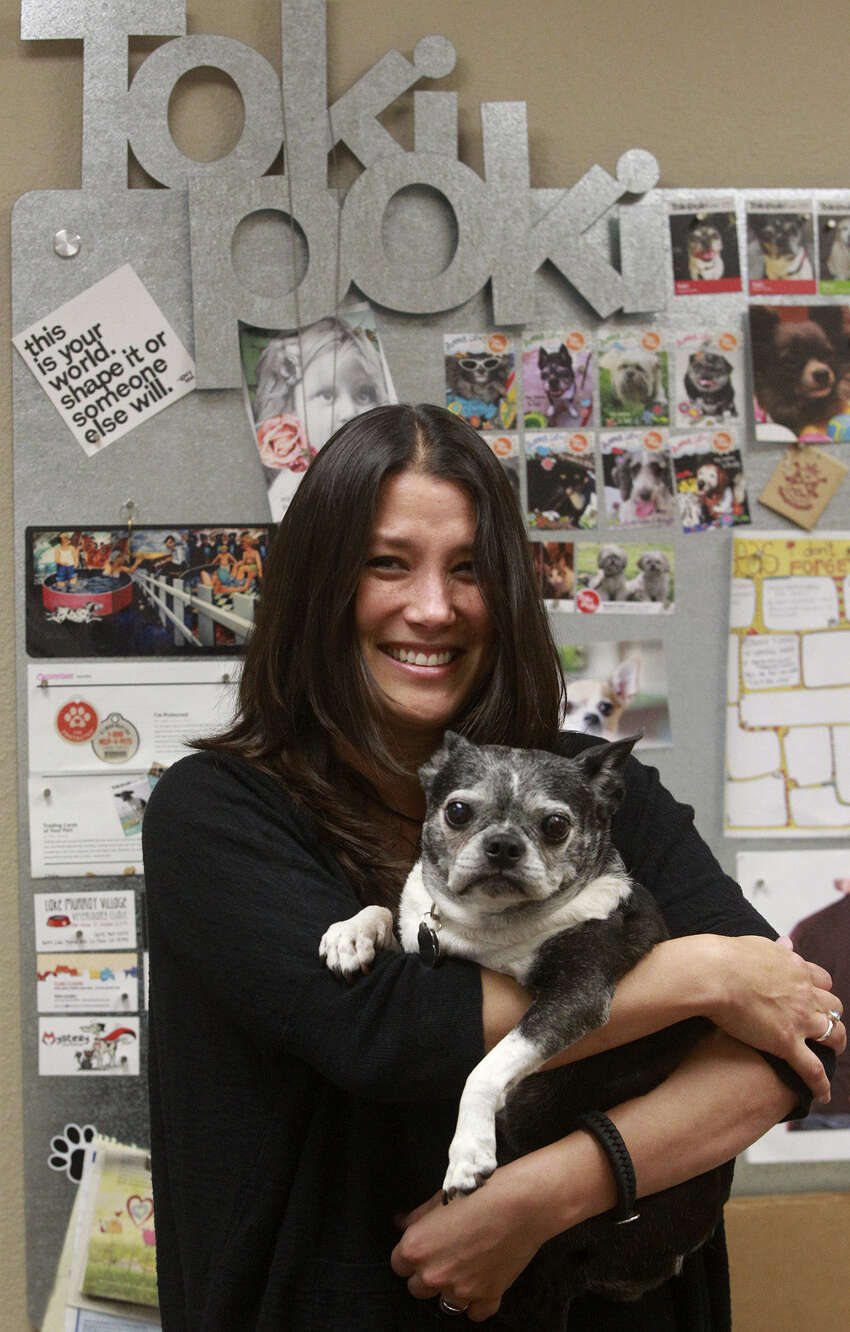 Christy Myhre spends time Tuesday May 13, 2014 with her dog Toki in her office at Toki Poki. Toki Poki makes pet trading cards for pet owners and gives them out to child patients at hospitals. Toki will be 15 years old this year.