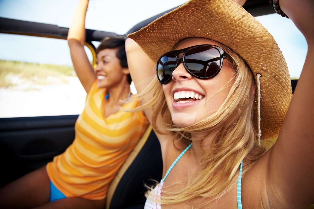 Cheerful friends enjoying a drive Women road trip vacation getaway car vehicle happy travel By: Joshua Hodge Photography Collection: Vetta