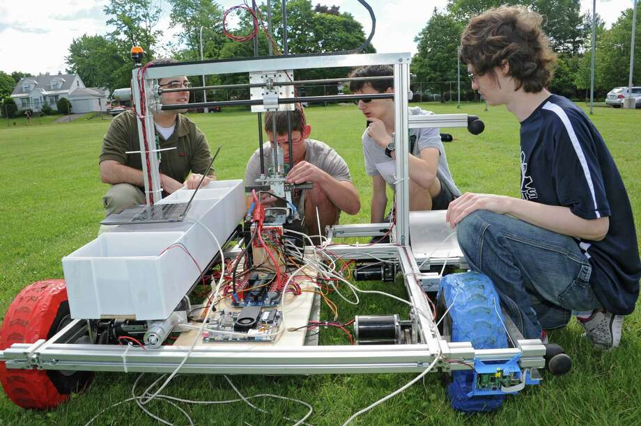 From left, Navy veteran Robert Svec looks over the sample return robot with Retrievers team members John DerBoghossian, Ethan Kranick and college mentor Ryan Mackenzie at Schenectady High School Friday, June 6, 2014 in Schenectady, N.Y. The Schenectady High School science team is competing in the NASA Sample Return Robot Centennial Challenge. Svec is a volunteer helping out with the computer software that runs the robot from a laptop. (Lori Van Buren / Times Union) Photo: Lori Van Buren / 00027231A