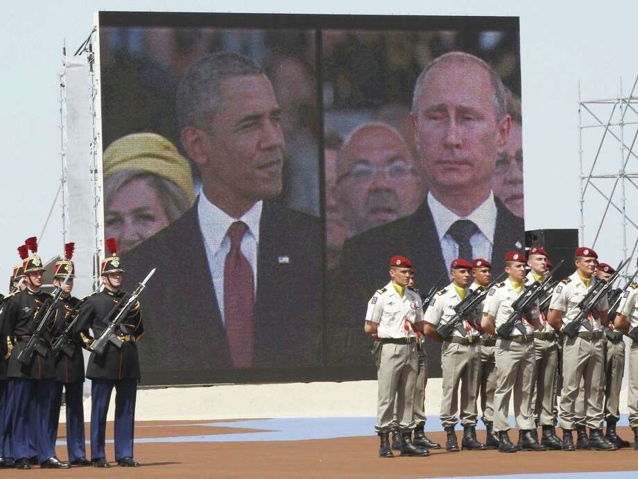 A large screen shows Russian President Vladimir Putin (R) and US President Barack Obama on a split-screen during an international D-Day commemoration ceremony on the beach of Ouistreham, Normandy, on June 6, 2014, marking the 70th anniversary of the World War II Allied landings in Normandy.  AFP PHOTO / POOL / CHRISTOPHE ENACHRISTOPHE ENA/AFP/Getty Images Photo: CHRISTOPHE ENA, Staff / AFP
