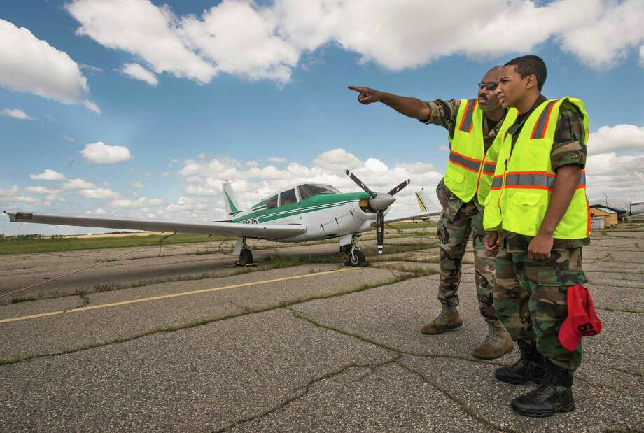 Captain Kenneth Fortes, lead instructor for the Bridgeport Military Academy air cadets flight operations after-school aviation program, instructs student Jessie Abrams on aircraft marshalling on the tarmac next to Sikorsky Memorial Airport as part of an after school aviation program at the Stratford Eagles squadron headquarters at Sikorsky Memorial Airport Stratford, CT on Saturday, May 31st, 2014. Photo: Mark Conrad / Connecticut Post Freelance