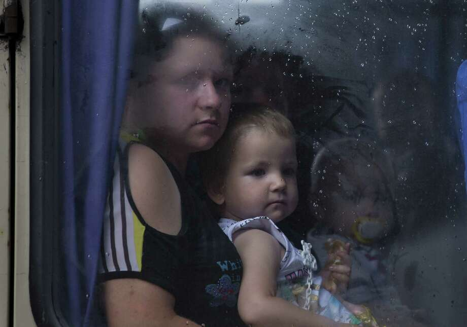 A mother and her children gaze out a bus window while leaving Slovyansk, Ukraine, 55 miles north of Donetsk. Photo: Alexander Zemlianichenko, Associated Press / AP