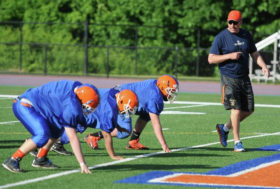 New Danbury Head Coach Mark Ecke directs the defensive linemen during Danbury football practice at Danbury High School in Danbury, Conn. Friday, June 6, 2014.  The team has a new coach for the 2014 season, now led by Mark Ecke. Photo: Tyler Sizemore / The News-Times