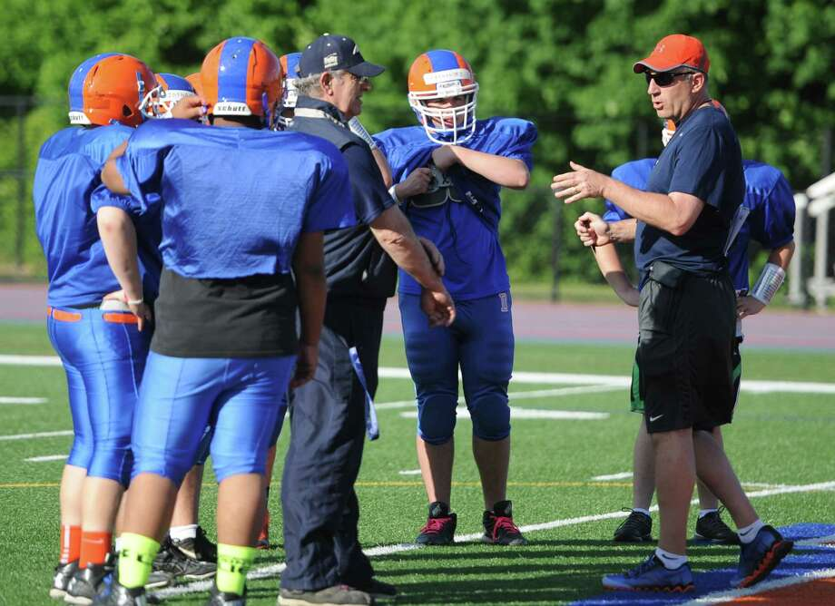 New Danbury Head Coach Mark Ecke, right, directs his players during Danbury football practice at Danbury High School in Danbury, Conn. Friday, June 6, 2014.  The team has a new coach for the 2014 season, now led by Mark Ecke. Photo: Tyler Sizemore / The News-Times