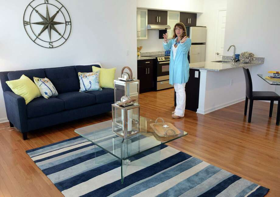 Carol Kuryla shows off one of the units in the Metro View apartments in Milford, Conn. developed by Metro Star Properties. Photo: Autumn Driscoll / Connecticut Post