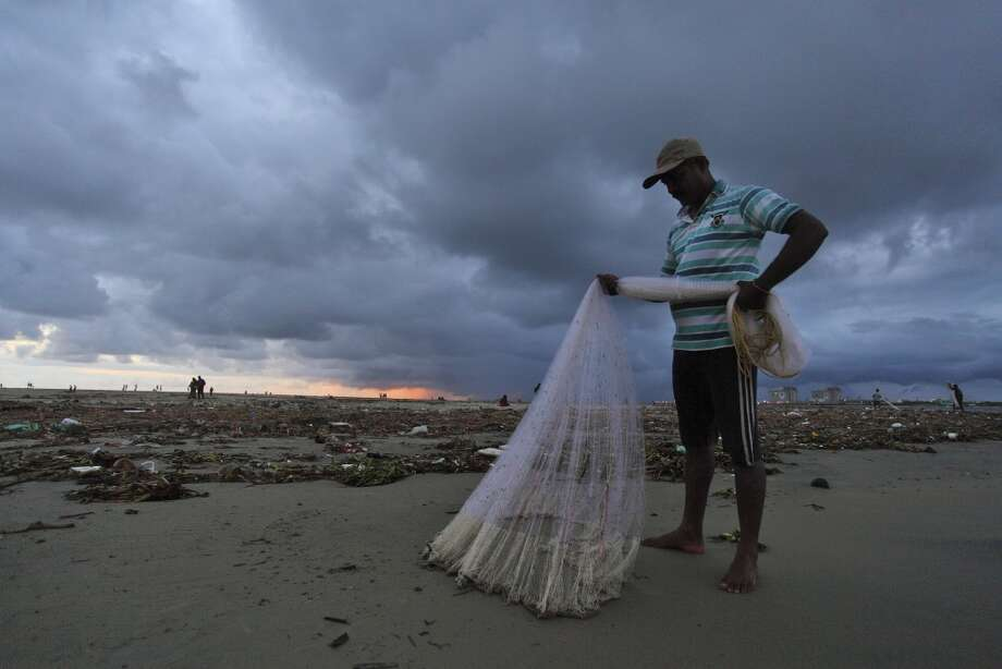 India: An Indian fisherman arranges his nets as monsoon clouds hover over the Kochi beach in Kerala, India, Friday, June 6, 2014. India's monsoon season, which runs from June to September, made a landfall at the Kerala coast Friday, according to local reports. Photo: Associated Press
