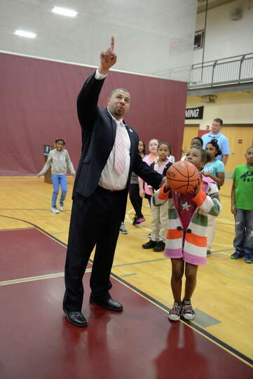David Brown, CEO of the Capital District YMCA, plays basketball with a young student at the North Al