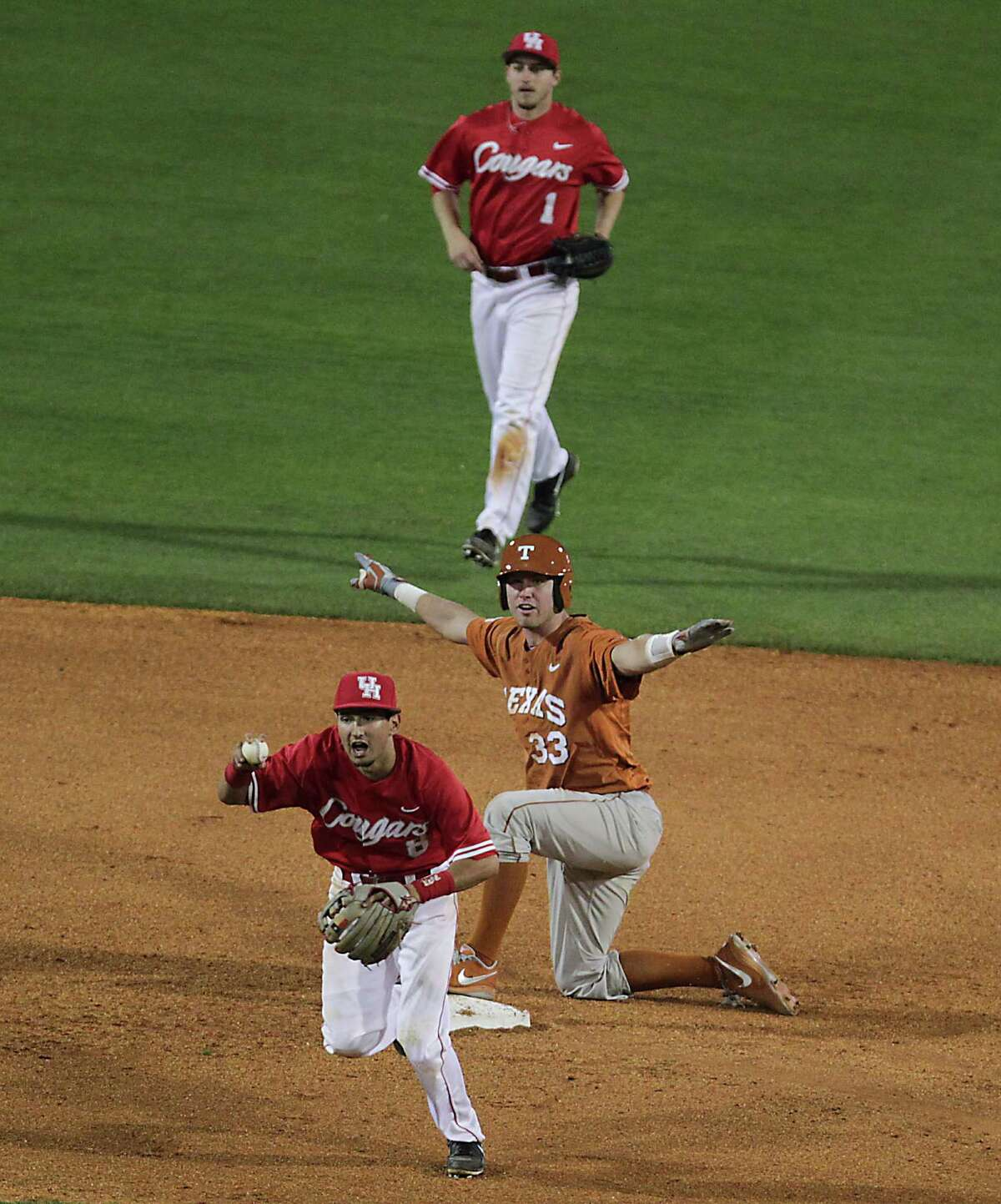In this March 19, 2013 photo, the University of Houston's Josh Vidales bottom, signals to an official as the University of Texas' Jeremy Montalbano middle motions he is safe as U of H's Landon Appling top, looks on during the sixth inning of college baseball game action at the University of Houston's Cougar Field in Houston. ( James Nielsen / Houston Chronicle )