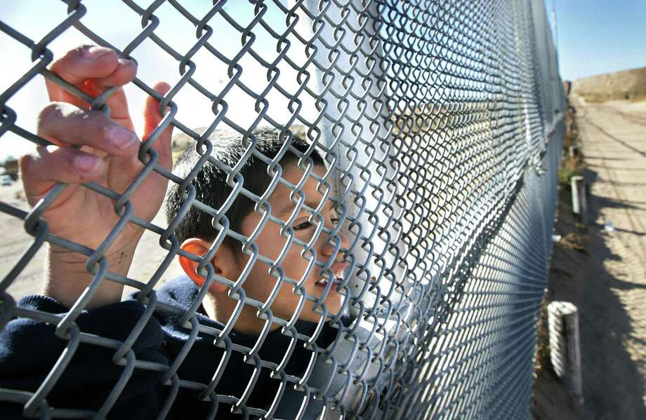 A young Juarez boy named Gerardo peeks through the border fence into Sunland Park, N.M. as Border Patrol vehicles pass by. Mexican authorities and advocates say that neither the violence in Mexico nor the increased vigilance by U.S. border patrol agents has affected the flow of undocumented immigrants under the age of 17.  (AP Photo/El Paso Times, Mark Lambie) Photo: Mark Lambie, MBO / El Paso Times